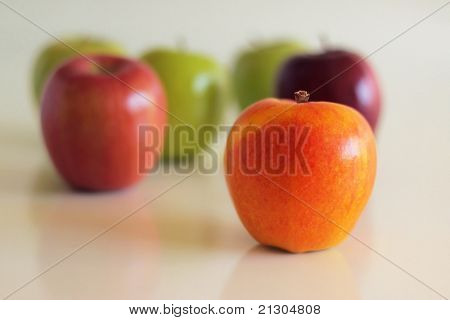 Group of varied colored apples with shallow depth of field against neutral reflective background