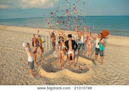 Casamento feliz recém-casado casal em torno de seus amigos de praia