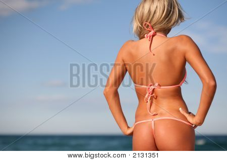 Sexy Bronzed Woman In Brief Bikini On The Beach With Back Turned