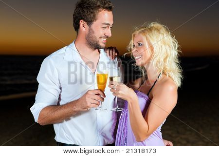 couple in the sunset, they are wearing smart casual clothes and drink champagne