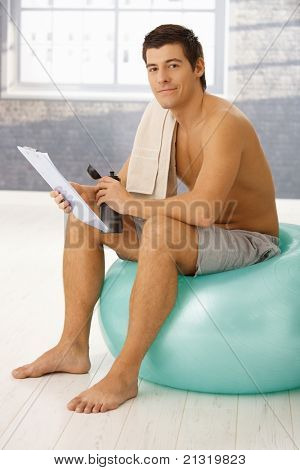 Handsome guy sitting on fit ball in gym in break of training, checking clipboard and drinking sports drink.?