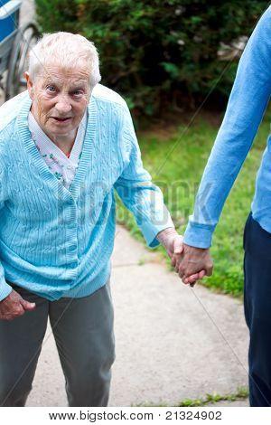 Senior lady walking with caregiver