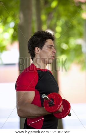 Strong man lifting weights at the park