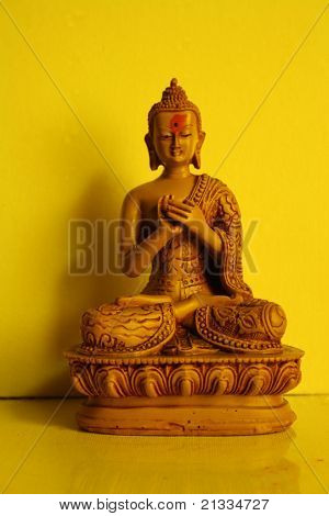 Buddha, against a yellow background.