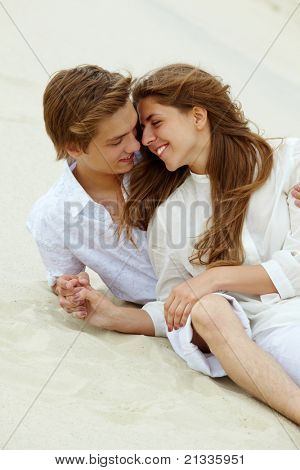 Photo of happy couple relaxing on sand during summer vacation