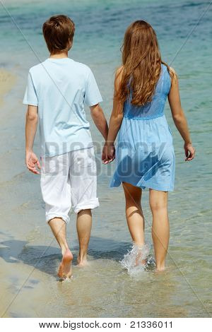 Photo of serene couple walking in water on summer vacation