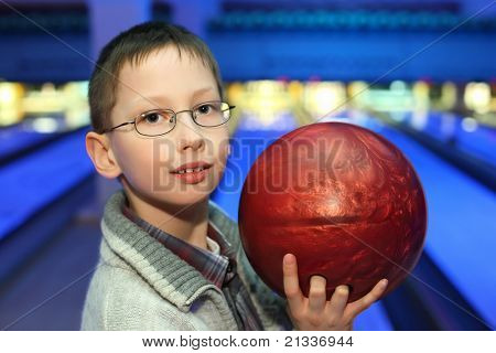 Portrait of boy in glasses, which hold ball for bowling