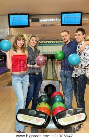 Four students stand near tenpin bowling with balls for playing bowling and smile, focus on girl in center