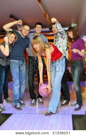 Girl prepares throw  ball in bowling club and friends it encourage scream and gestures, focus on girl in center