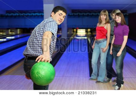 Young man prepares throw ball on path for bowling and three girls look on him, focus on man
