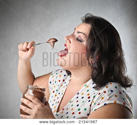 Glutton woman eating chocolate cream from a jar with a knife