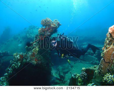 A Scuba Diver Swims Through A Sunken Pier.