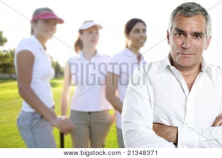 senior golfer man portrait in green course with three women in background