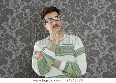 nerd  silly man with pensive expression over retro wallpaper background