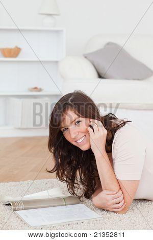 Wunderschöne Französin, eine Zeitschrift lesen, beim liegen auf dem Teppich im Wohnzimmer
