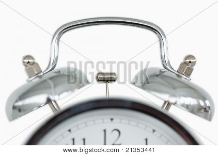 Close up of an old fashioned alarm clock against a white background