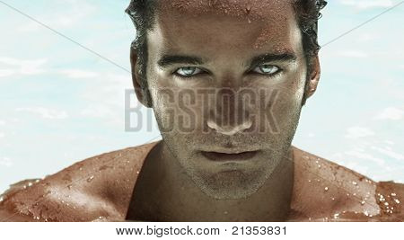 Highly detailed closeup portrait of a young good looking man's face with bright catch light reflections in blue eyes against modern wet background