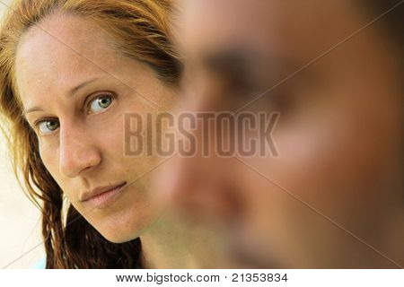 Shallow depth of field portrait of a couple with focus on the woman looking at her mate's profile