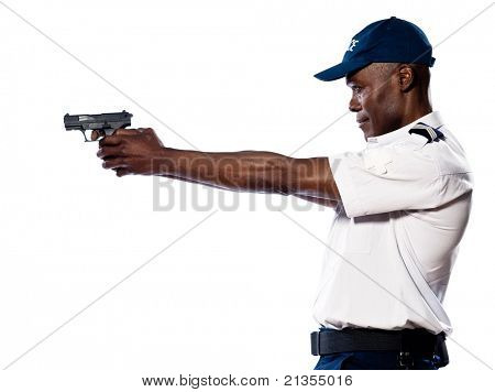 Side view of an afro American police officer aiming gun in studio on white isolated background