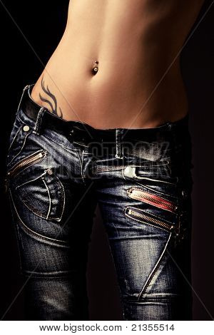 close up of woman body in jeans, studio dark background, vertical
