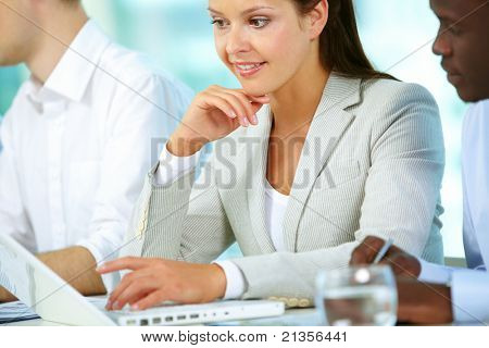 Pretty woman sitting in front of laptop and looking at its screen