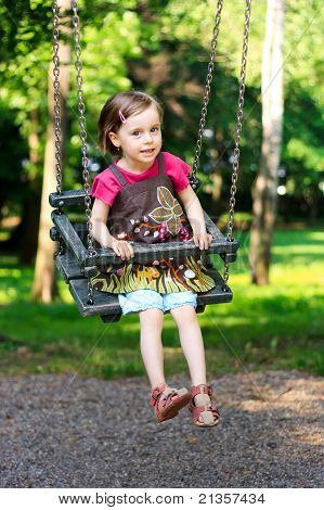 A Beautiful Little Girl Swinging At The Playground In The Park