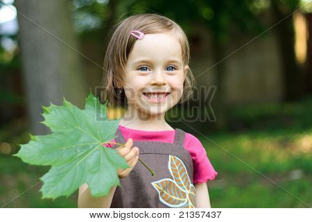 Portrait Of Cute Little Girl With A Maple Leaf