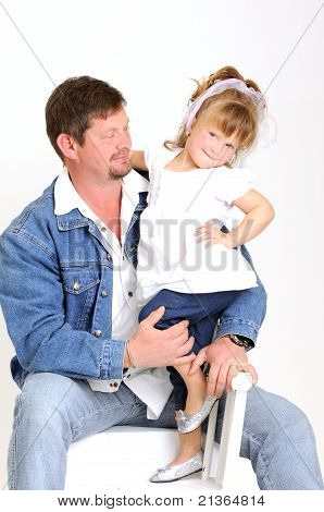 young father dressed in jeans and toddler girl dressed in white hugging and smiling lovingly