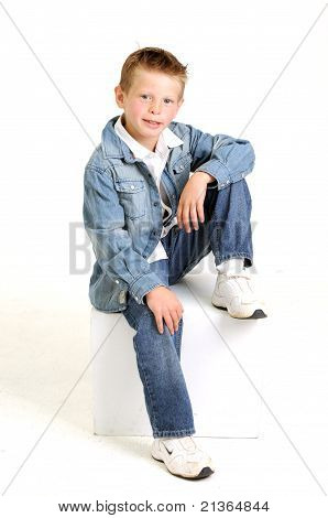 young attractive boy wearing a blue jean jacket sitting and smiling