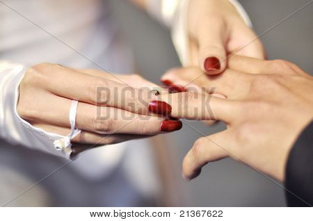 A bride is putting a wedding ring on groom's hand