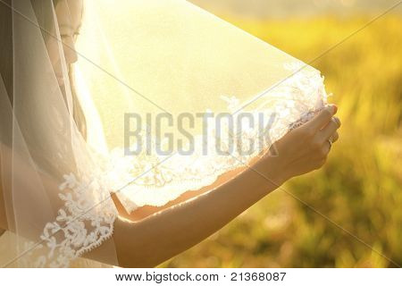 Asian bride under veil at outdoor in a morning surrounding by golden sunlight