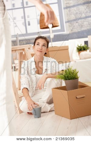 Young couple moving home, woman sitting on floor with boxes around, man hanging keys front of her.?