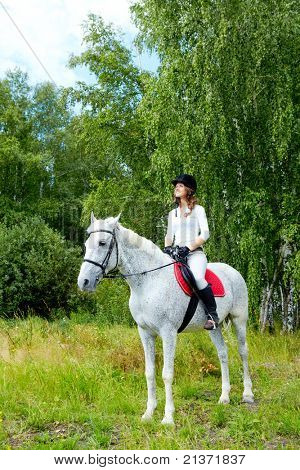 Image of happy female jockey sitting on appaloosa horse outdoors