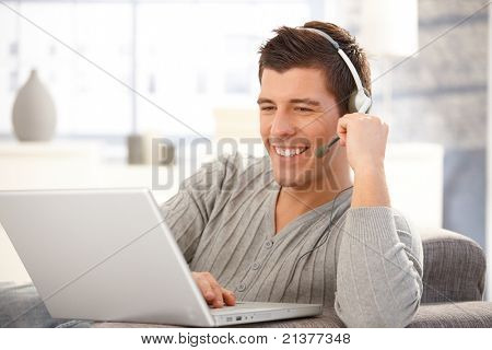 Portrait of handsome young man using laptop computer with headset, laughing.?