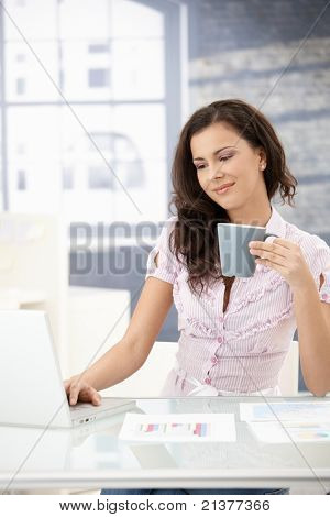 Pretty young girl working on laptop, sitting at desk in bright office, smiling, drinking tea.?