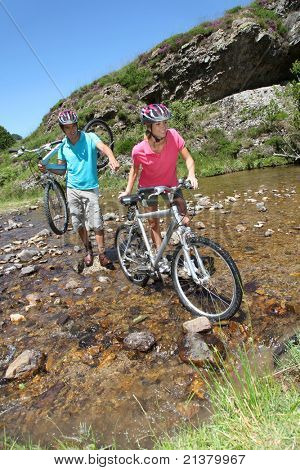Couple crossing river with mountain bikes