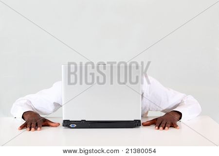 Businessman hiding behind laptop computer