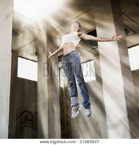 Menina jovem gostosa dançarina no ar elevando-se para a luz brilhante no teto no antigo salão de fábrica sujo.