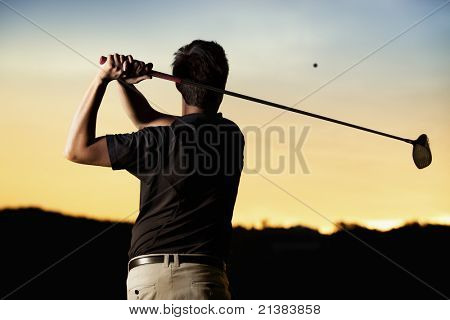 Close up professional golf player in black shirt teeing-off ball in twilight, view from behind.