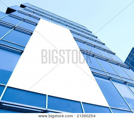 blue glass wall with blank placard of skyscraper