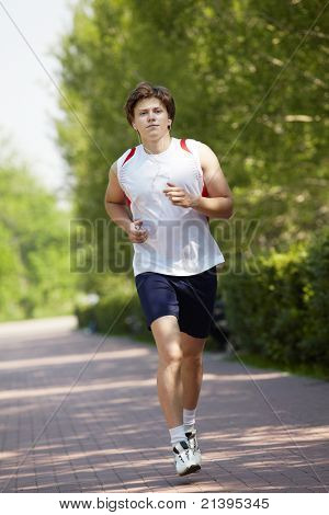 Portrait of a young man jogging with a walkman in park