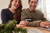 Young Couple Shopping Online For Christmas poster