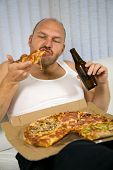 stock photo of couch potato  - Unattractive overweight man eating a big slice of pizza and drinking beer - JPG