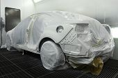 picture of paint spray  - Car covered of protective mask stands in the spray booth - JPG