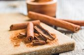 Cinnamon sticks and milled cinnamon spice on old table. poster