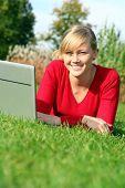 Girl Using Laptop Outdoors poster