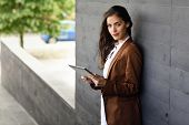 Businesswoman With Tablet Computer Standing Outside Of An Office Building. poster