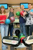 Fellows and girls stand near tenpin bowling with balls for playing bowling and laugh merrily, focus