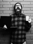 Bearded Brutal Caucasian Hipster Holding Laptop With Cup poster