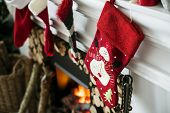 Christmas stockings hanging on a chimney poster